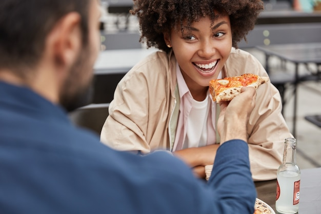 Horizontal cropped view of cheerful black woman with afro hairstyle eats delicious italian pizza from boyfriends hands Free Photo