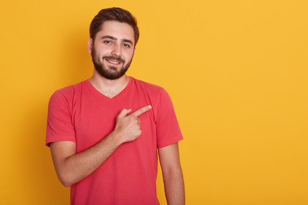 Horizontal handsome unshaven male, dressed in casual red t shirt,, pointing with index finger aside, shows copy space for your advertisment or promotion text. Free Photo