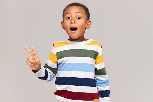 L'immagine orizzontale del ragazzo africano emozionante divertente che tiene la bocca spalancata è sorpresa di vedere qualcosa di inaspettato, facendo un gesto di pace. bambino nero emotivo che mostra il segno di vittoria e che esclama Foto Gratuite