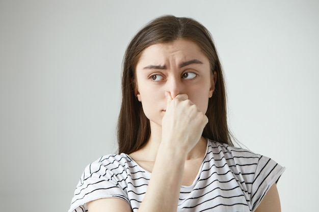 Horizontal isolated  frustrated frowning young dark haired woman having disgusted look, pinching her nose and holding breath because of unpleasant disgusting smell, odor or stink Free Photo