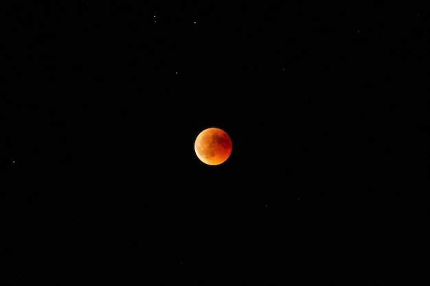 Horizontal long shot of an orange and red moon in the dark sky at night Free Photo