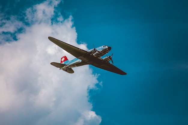 Horizontal low angle shot of a silver airplane under the beautiful cloudy sky Free Photo