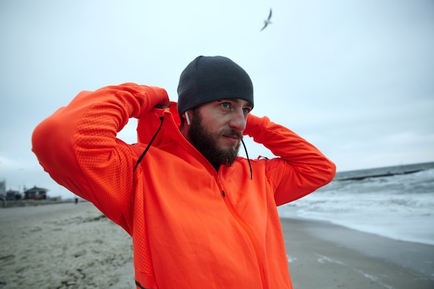 Horizontal photo of handsome young bearded male dressed in sportswear holding hood with raised hands and looking at sea with calm face, walking along seaside before working day Free Photo