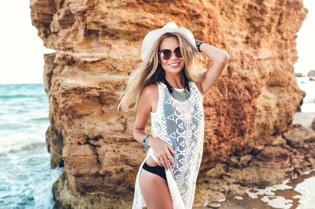 Горизонтальное фото красивой блондинки с длинными волосами в шляпе, позирующей перед камерой на скалистом пляже. она улыбается. Бесплатные Фотографии