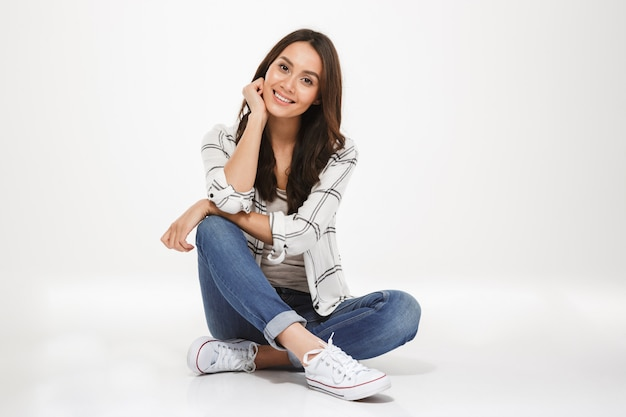 Horizontal picture of brunette woman with brown hair sitting with legs crossed on the floor and looking on camera with smile, isolated over white wall Free Photo