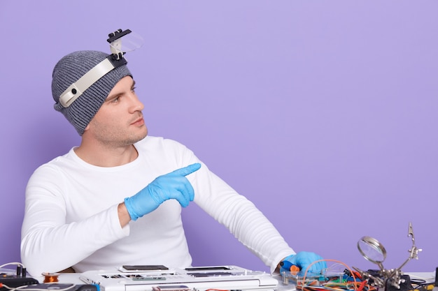Horizontal picture of young professional electronic engineer fixing laptop, making gesture, looking aside, using equipment Free Photo