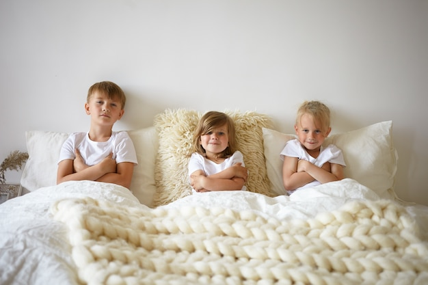 Horizontal portrait of adorable pretty baby girl relaxing in bed between her two elderly brothers. charming european children siblings crossing arms, refusing to get up early in the morning Free Photo