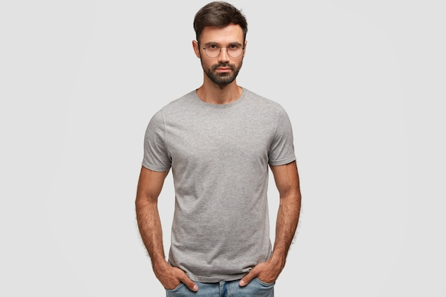 Horizontal portrait of attractive bearded male with serious expression, dressed in casual grey t-shirt, keeps hands in pockets, shows new clothes, isolated over white wall. people, style concept Free Photo