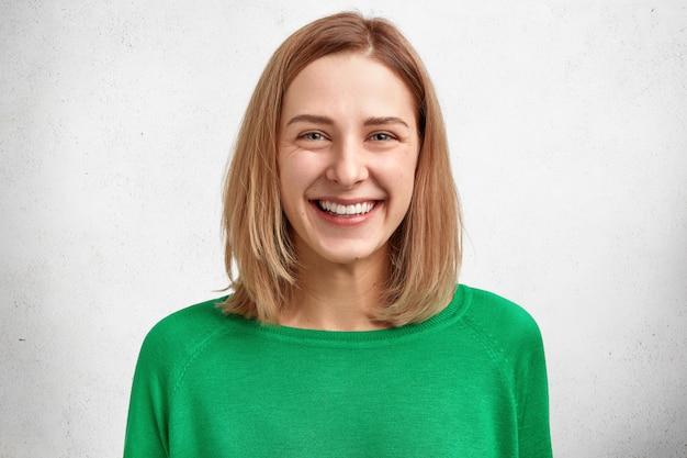 Ritratto orizzontale di bello giovane modello femminile allegro con l'acconciatura bobbed, sorriso gentile piacevole, pelle sana, indossa un maglione verde Foto Gratuite