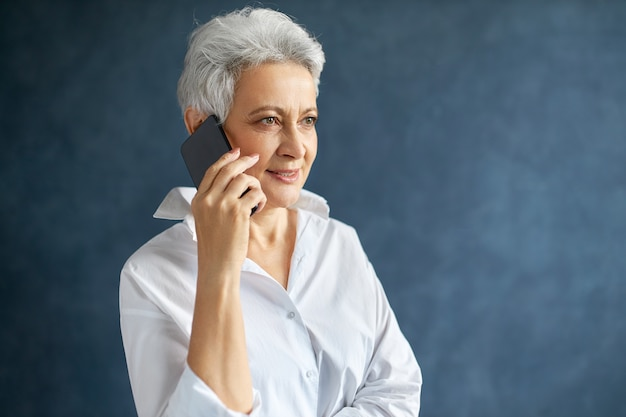 Ritratto orizzontale del responsabile femminile caucasico invecchiato centrale occupato nel telefono delle cellule della tenuta della camicia bianca Foto Gratuite
