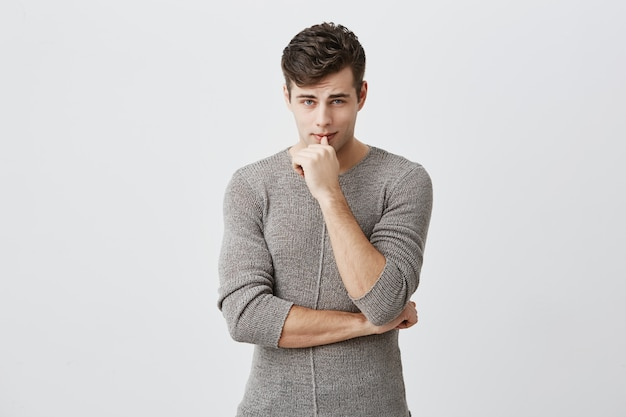 Free Photo Horizontal Portrait Of Confident Serious Attractive Caucasian Man Keeping Hand Under Chin Touching Lips Wearing Casual Clothes Thoughtful Male Student Poses At Studio