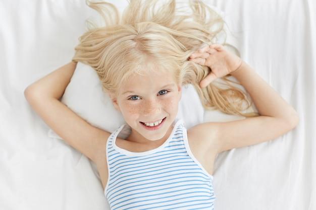 Ritratto orizzontale della ragazza carina con gli occhi blu brillanti, la faccia lentigginosa e il sorriso gentile, rilassante nel letto, sdraiato sul comodo cuscino bianco Foto Gratuite