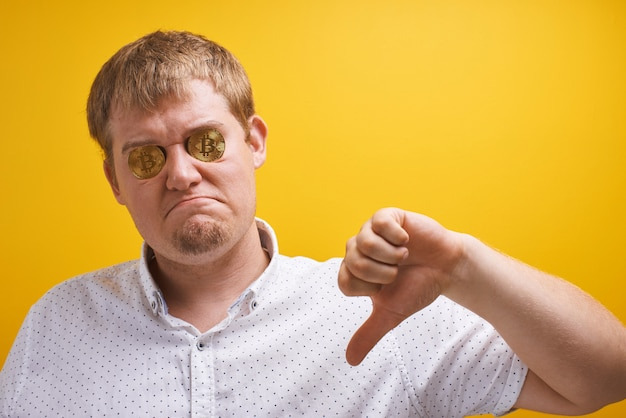 Horizontal portrait of fat guy with bitcoins in his eyes on a yellow background. digital virtual currency concept, defrauded investor, cryptocurrency fall on internet market Premium Photo