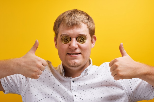 Horizontal portrait of joyful fat guy with bitcoin in the eyes on yellow background. digital virtual currency concept, cryptocurrency growth on internet market, wealth and success Premium Photo