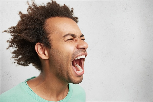 Horizontal portrait of man with dark skin and afro hairstyle screams in despair, opens mouth widely, being in panic Free Photo