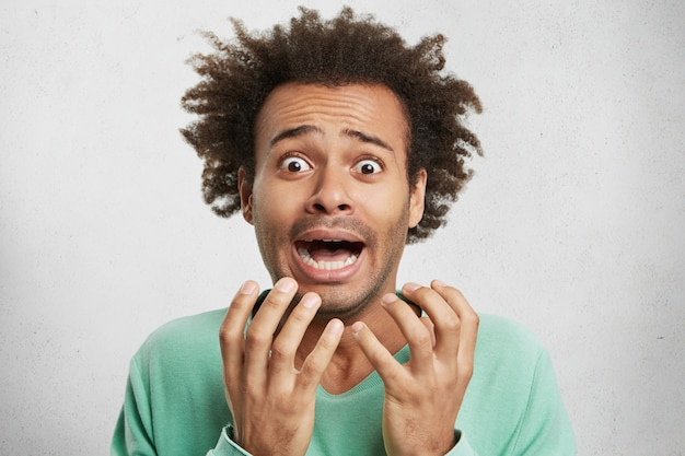 Horizontal portrait of nervous puzzled mixed race man gestures in panic, has disturbed and petrified expressions Free Photo