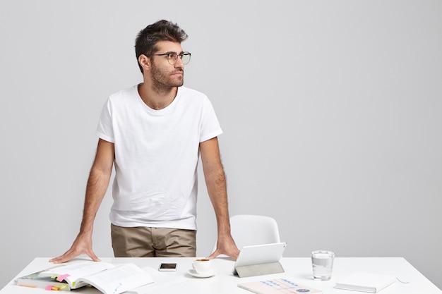 ひげを生やしたビジネスマンの水平方向の肖像画はカジュアルな服とメガネを着ています。 無料写真