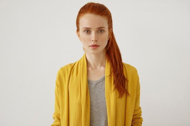 そばかすをもつ美しい若い女性の水平方向の肖像画angジンジャーポニーテール、黄色の服を着て、唇全体と緑の輝く目をして、自信を持って直接見ます 無料写真
