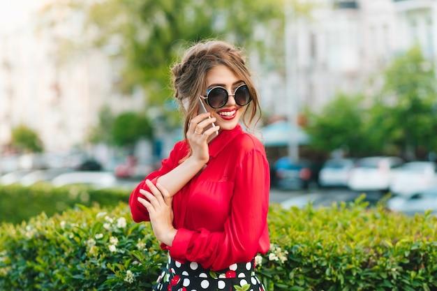 Горизонтальный портрет красивой девушки в солнечных очках, стоящих в парке. она носит красную блузку и красивую прическу. она говорит по телефону. Бесплатные Фотографии