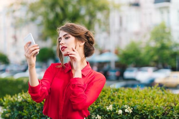Горизонтальный портрет красивой девушки, стоящей в парке. она носит красную блузку и красивую прическу. она смотрит на телефон в руке и мечтает. Бесплатные Фотографии