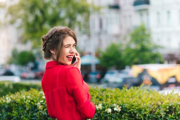 Горизонтальный портрет красивой девушки, стоящей в парке. она носит красную блузку и красивую прическу. она говорит по телефону и смотрит в камеру. Бесплатные Фотографии