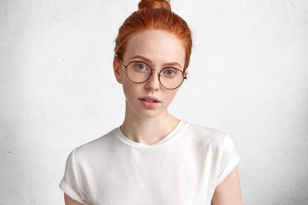 大きな丸い眼鏡の深刻な兄弟分の女性の水平方向の肖像画は、カメラに直接神秘的な表情で見える 無料写真