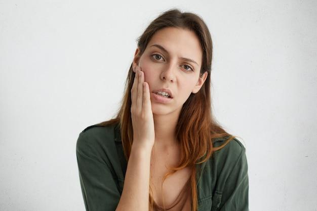 Ritratto orizzontale di donna abbastanza triste con luminosi occhi scuri e capelli lisci tenendo la mano sulla guancia guardando sconvolto Foto Gratuite