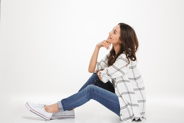 Horizontal portrait of smiling young woman with brown hair sitting in profile on the floor and propping up head with hand, isolated over white wall Free Photo