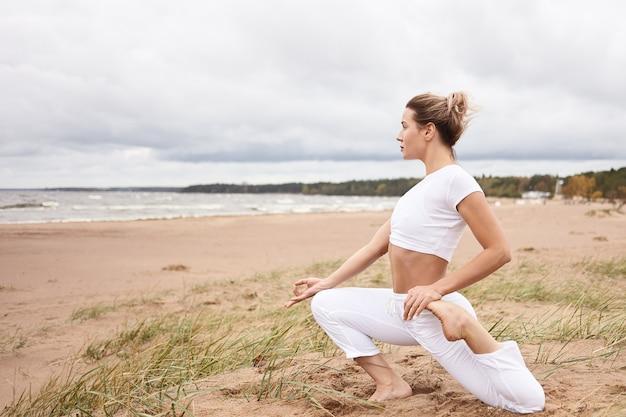 Profilo orizzontale della bella giovane donna bionda atletica che lavora sulla spiaggia sabbiosa, di fronte al mare, facendo esercizi di stretching durante la pratica dello yoga, seduti in eka pada rajakapotasana Foto Gratuite