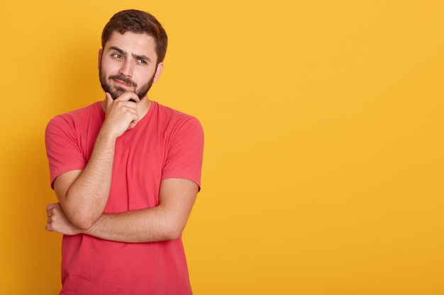 Horizontal serious unshaven male dresses casual red t shirt, keeps hand under chin, looks aside with serious facial expression, thinks about something, poses on yellow wall with free space. Free Photo