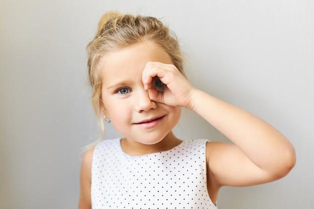 Colpo orizzontale di adorabile bella ragazza in abito bellissimo in posa guardando attraverso il binocolo fatto della sua mano, collegando il pollice con l'indice bambino femmina divertente carino divertendosi, spiare Foto Gratuite