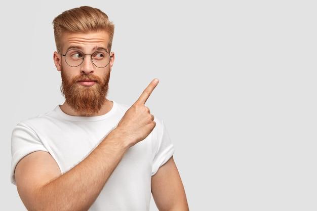 Inquadratura orizzontale di attraente maschio caucasico ha i capelli e la barba color zenzero, i punti con il dito anteriore a parte, vestito con una maglietta in un colore con parete Foto Gratuite