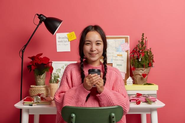Inquadratura orizzontale di attraente ragazza coreana tiene caffè da asporto, si siede su una sedia vicino al suo posto di lavoro, finisce di lavorare, adesivi sul muro rosa. Foto Gratuite