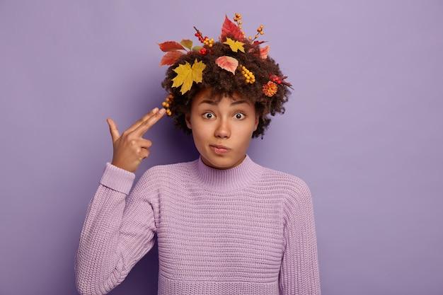 Inquadratura orizzontale di bella donna afroamericana perplessa spara nel tempio con le dita, mostra il gesto di suicidio, vestito con un maglione caldo, come foglie gialle nei capelli Foto Gratuite