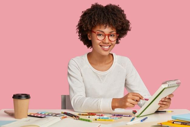 Colpo orizzontale di allegro pittore afro africano indossa occhiali con bordo rosso, fa schizzi in quaderno a spirale con la matita, gode di una bevanda aromatica, circondato da fermo, sorride positivamente Foto Gratuite