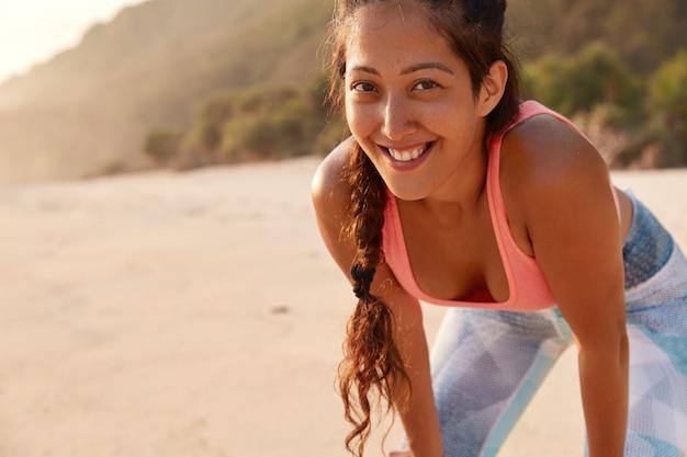 Inquadratura orizzontale della donna allegra fitness ha la pelle lentigginosa, treccia scura, vestita con abiti sportivi, sorriso piacevole Foto Gratuite