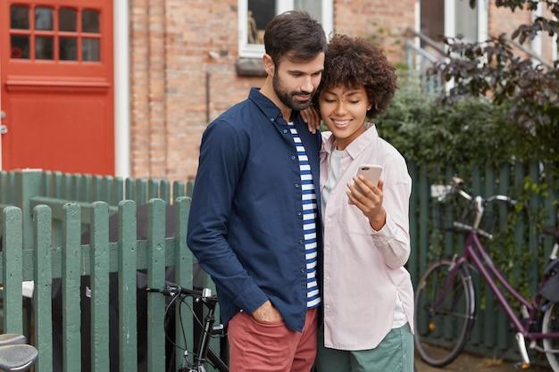 Colpo orizzontale di uomo e donna giovane razza mista allegra leggere le informazioni sul telefono cellulare Foto Gratuite
