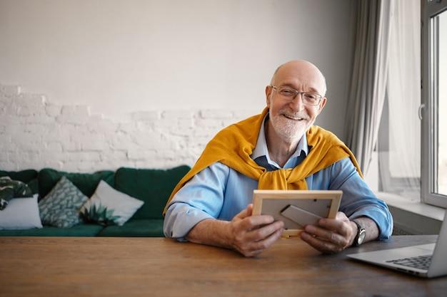 Inquadratura orizzontale di allegro uomo d'affari alla moda sessantenne che indossa occhiali rettangolari seduto davanti al computer portatile aperto, tenendo il ritratto di famiglia in cornice e sorridendo felicemente Foto Gratuite