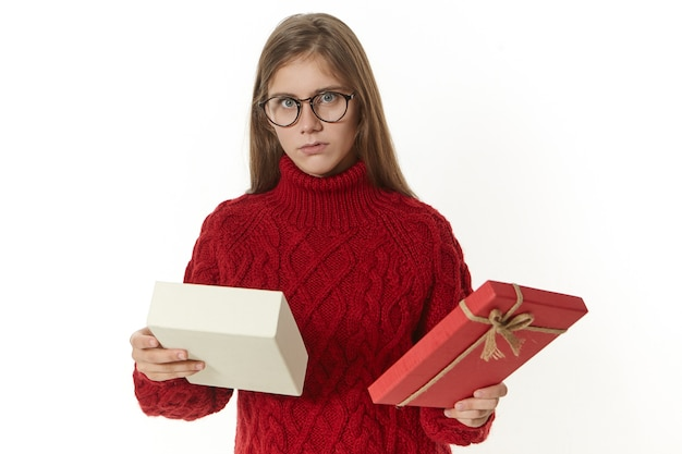 Horizontal shot of displeased or confused young woman wearing spectacles and knitted sweater posing holding open box, being puzzled while receiving wrong present that she does not like Free Photo
