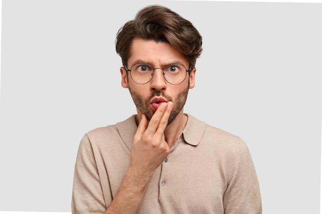 Horizontal shot of emotive puzzled angry european man holds chin and looks in bewilderment, has serious expression Free Photo