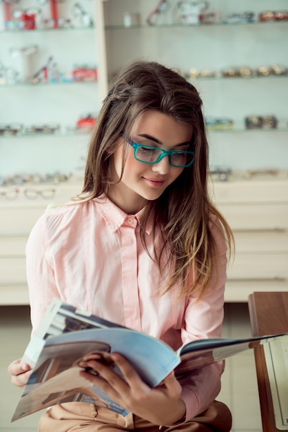 Horizontal shot of good-looking caucasian female customer sitting in trendy prescribed glasses, reading magazine and smiling, waiting in queue for eye doctor for regular sight check-up Free Photo