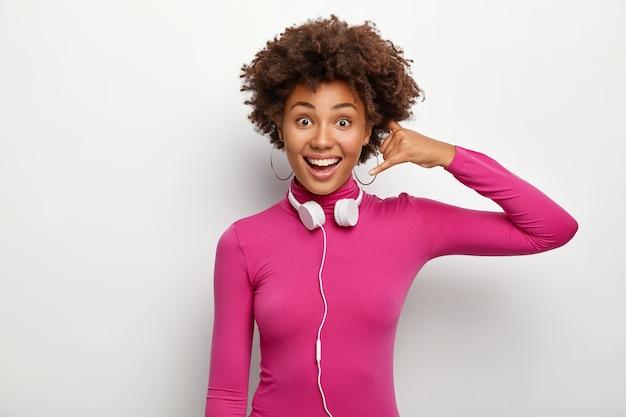 Il colpo orizzontale della donna dalla pelle scura felice fa il gesto di chiamata, guarda positivamente, indossa le cuffie intorno al collo, posa su sfondo bianco, si sente soddisfatto. linguaggio del corpo Foto Gratuite