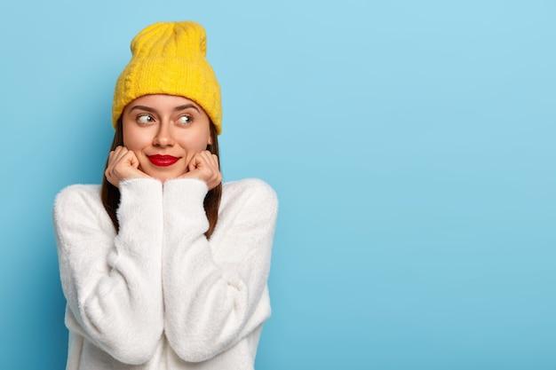 Colpo orizzontale di donna europea sognante felice indossa trucco minimo, rossetto rosso, guarda da parte, vestita con cappello giallo e maglione bianco, posa su sfondo blu, affascinata e soddisfatta Foto Gratuite