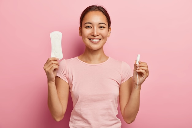 Horizontal shot of happy korean woman holds sanitary napkin and tampon, demonstrates intimate products for women health, smiles gently , dressed in casual outfit, has critical days. Free Photo