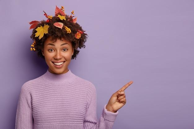 L'inquadratura orizzontale della donna felice aiuta a scegliere la scelta migliore, punta l'indice su uno spazio vuoto, sorride piacevolmente, indossa un maglione caldo, ha l'acconciatura riccia con fogliame autunnale Foto Gratuite