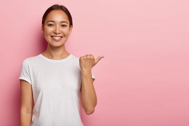 Inquadratura orizzontale della giovane donna asiatica felice indica lo spazio della copia, mostra qualcosa di buono, indossa una maglietta bianca, aiuta a scegliere la scelta migliore, consiglia il prodotto, modelli su un muro rosa Foto Gratuite