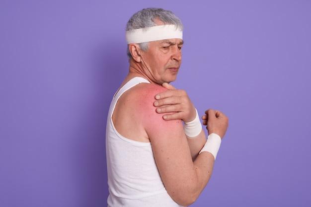 Colpo orizzontale dell'uomo senior ferito che posa lateralmente, maschio maturo con la fascia capa bianca, sportrsman anziano Foto Gratuite