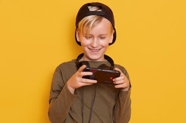 Colpo orizzontale del ragazzino che indossa berretto nero e felpa con cappuccio verde, in posa con il cellulare in mano, bambino alla moda giocando giochi online. Foto Gratuite