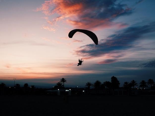 パラモーターパラシュートで滑空する人とビーチの水平方向のショット 無料写真