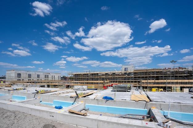澄んだ青い空の下に足場がある建設現場の水平方向のショット 無料写真
